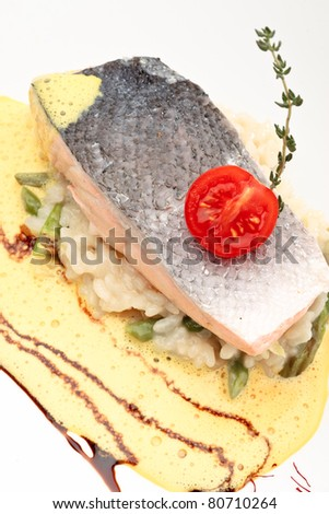 Salmon in wine decorated with tomato and rice on a white background - stock photo
