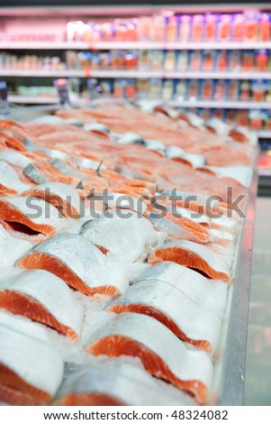 Salmon on cooled market display, shelves in blurred background - stock photo