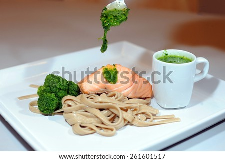 Salmon on noodle with broccoli. - stock photo
