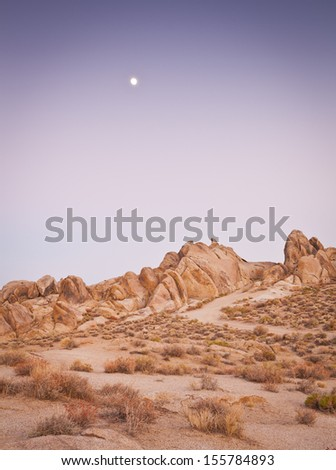 Salmon pink hues of sunset illuminate the weird and wonderful rock formations of the Alabama Hills in California, which is a popular filming location for television and movie productions. - stock photo