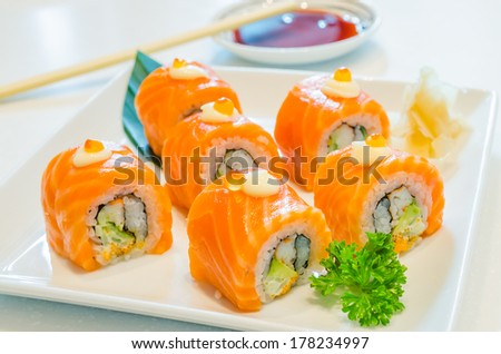 Salmon roll sushi with salmon egg on top in white dish - stock photo