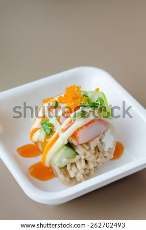 Salmon roll sushi with shrimp egg on top in white dish - stock photo