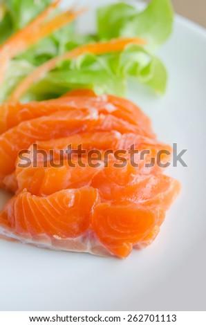 salmon sashimi with fresh salad on white dish - stock photo