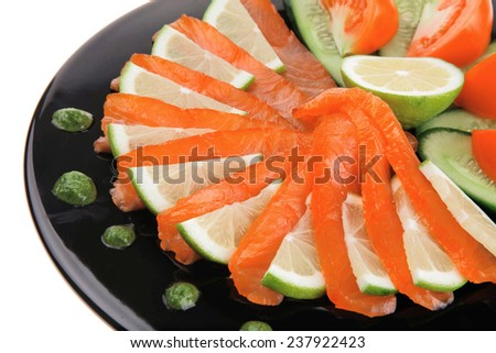 salmon slices and tomatoes on black plate - stock photo