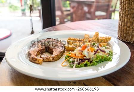 salmon steak and mashed potato on wood table - stock photo