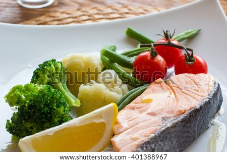 Salmon steak and steamed vegetables, served on a wooden background. Lenten  healthy food. Top view on dietary fish dish with salmon and vegetables - stock photo