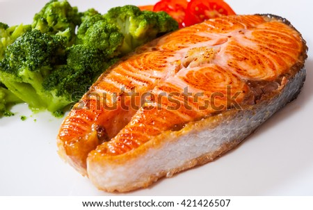 Salmon steak fish fillet with broccoli on plate - stock photo