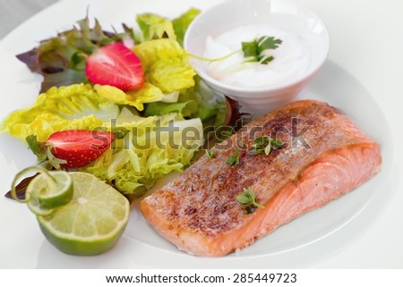 Salmon steak in white dish with vegetables - stock photo