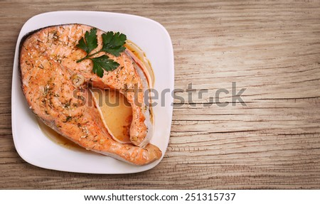 Salmon steak on plate over wooden background - stock photo