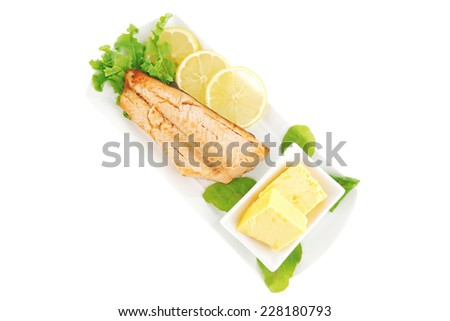 salmon steak on white plate with butter - stock photo