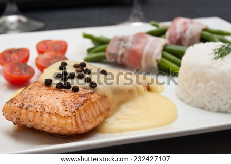 salmon steak with hollandaise sauce and rice cherry tomatoes and green beans - stock photo