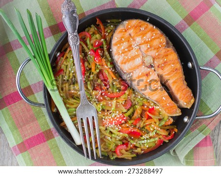 Salmon steak with vegetables in pan portion - stock photo