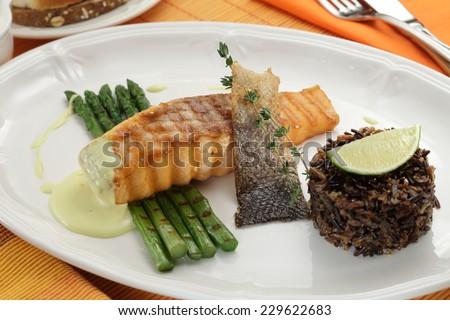 Salmon steak with wild rice and asparagus. Mediterranean cuisine - stock photo
