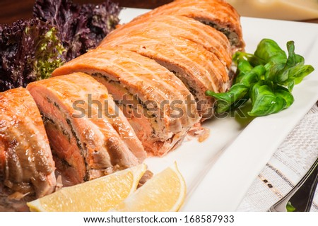 Salmon stuffed with cheese and mushrooms with lettuce and lemon - stock photo