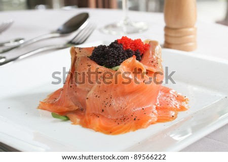 Salmon volcano salad with rocket, topped with red and black caviar - stock photo
