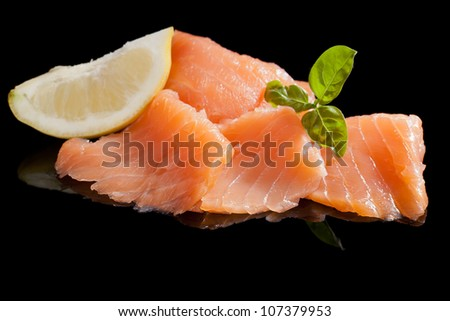 Salmon with lemon and basil isolated on black background. Luxurious seafood concept. - stock photo