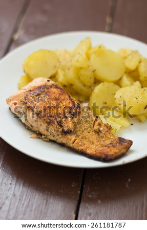 Salmon with potatoes on white plate - stock photo