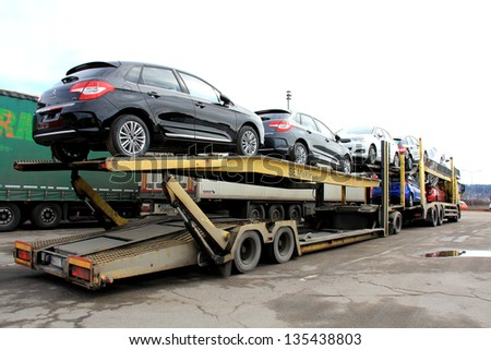 SALO, FINLAND - APRIL 14, 2013: Car carrier delivering cars in Salo, Finland on April 14, 2013. European car sales fall 10,2% in March 2013 from 3/2012, marking the 18th consecutive month of declines. - stock photo