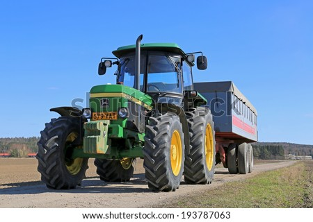 SALO, FINLAND - APRIL 20, 2014: John Deere 2850 utility tractor and agricultural trailer. The model 2850 was manufactured between 1986-1994 in Germany and Argentina. - stock photo