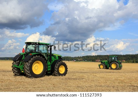 SALO, FINLAND - AUGUST 18: New John Deere tractors on display at the annual soil preparation and harvesting event Puontin peltopaivat at Puonti field in Salo, Finland August 18, 2012. - stock photo