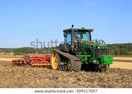 SALO, FINLAND - AUGUST 21, 2015: Unnamed farmer cultivates the field with John Deere 8345RT tracked tractor at setting up of Puontin Peltopaivat Agricultural Harvesting and Cultivating Show. - stock photo