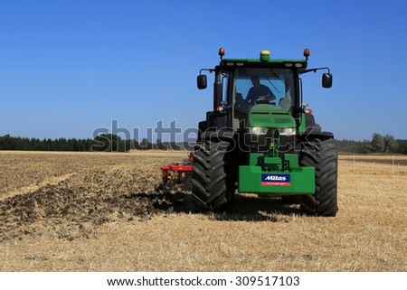 SALO, FINLAND - AUGUST 22, 2015: Unnamed farmer demonstrates cultivating field with John Deere 8370R tractor and cultivator at Puontin Peltopaivat Agricultural Harvesting and Cultivating Show. - stock photo