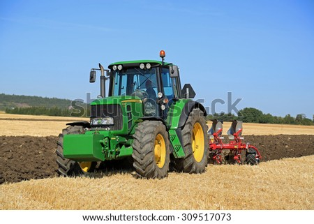 SALO, FINLAND - AUGUST 21, 2015: Unnamed farmer operates John Deere 6630 tractor and Agrolux plow on field at setting up of Puontin Peltopaivat Agricultural Harvesting and Cultivating Show. - stock photo