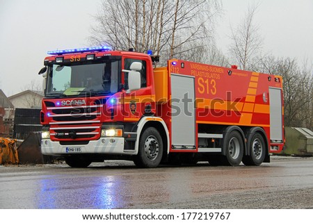 SALO, FINLAND - FEBRUARY 16, 2014: Scania P360 Fire engine with flashing lights at the fire scene of Salo Cement Plant. The plant was completely destroyed in the fire. - stock photo