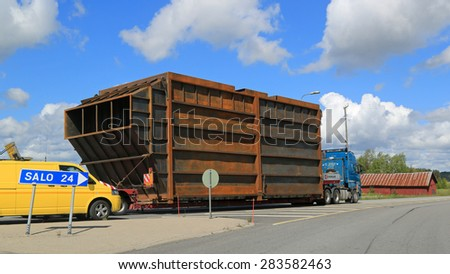 SALO, FINLAND - MAY 31, 2015: Pilot cars stop traffic to lead a wide load against traffic in a narrow roundabout. Route surveys and planning are necessary prior to exceptional load transport. - stock photo