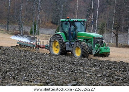 SALO, FINLAND - OCTOBER 25, 2014: Unnamed farmer ploughing a field with John Deere 8100 tractor. John Deere 8100 was manufactured in 1995-1999 and it has JD 7.6L or 8.1L 6-cyl diesel engine. - stock photo
