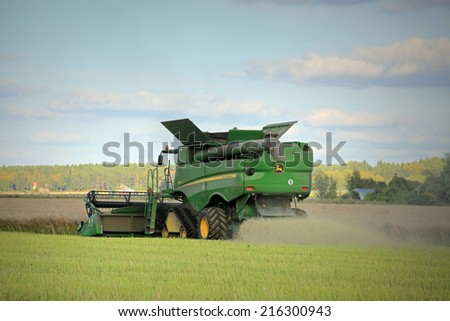 SALO, FINLAND - SEPTEMBER 6, 2014: John Deere s670i Combine on field in the evening harvesting Rapeseed. EC estimates the European Rapeseed crop grow by 7% in 2014. - stock photo