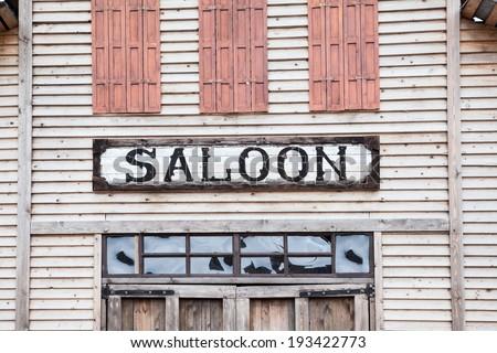 Saloon inscription on wooden building facade - stock photo