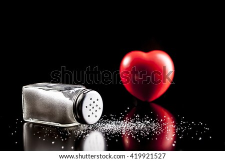 Salt and heart isolated on black background with reflection - stock photo