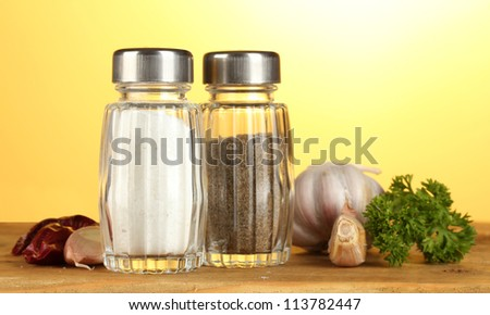 Salt and pepper mills, garlic and parsley on wooden table on yellow background - stock photo