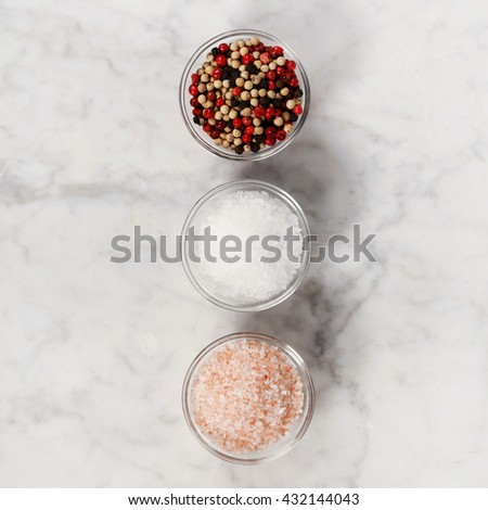 Salt and pepper on white marble background - stock photo