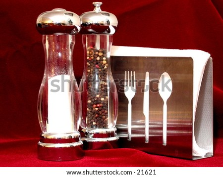 Salt and pepper shakers and napkin holder. - stock photo