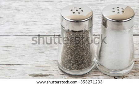 Salt and peppercorn powder in glass condiment shaker over wooden background - stock photo