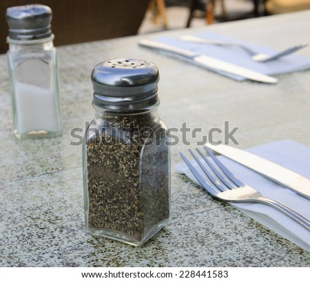 Salt cellar, pepper caster, forks and knives on granite table at an outdoor restaurant. - stock photo