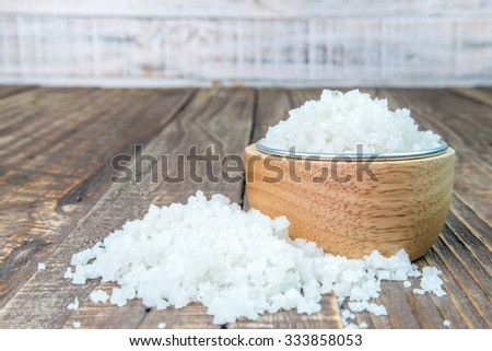 Salt in a cup on a wooden background. - stock photo