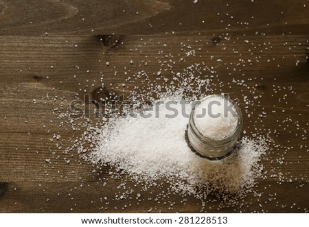 Salt in a glass jar on a wooden background, top view, selective focus - stock photo