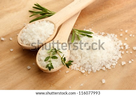 salt in spoons with fresh  rosemary and thyme on wooden background - stock photo