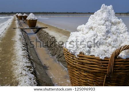salt in the bamboo basket on the ground near salt pan, Thailand - stock photo