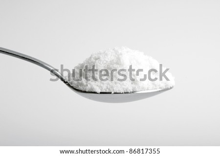 salt in the spoon on white - stock photo