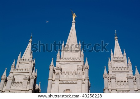 Salt Lake City Temple, golden statue and the Moon on the morning blue sky - stock photo