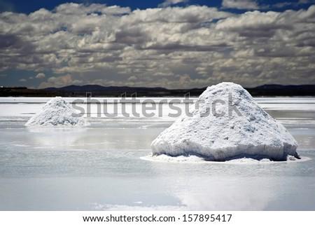Salt mining triangular piles on the surface of Salar de Uyuni salt lake, Bolivia - stock photo