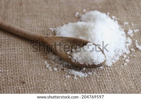 Salt on wooden spoon on jute sackcloth background - stock photo