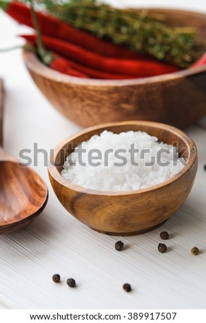 Salt, pepper, chili and thyme in wooden bowls on white rustic wooden table - stock photo
