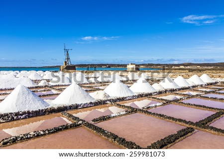salt piles in the saline of Janubio in Lanzarote with old toteen wind mill under blue sky - stock photo