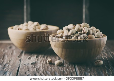 Salt pistachio nuts in the wooden bowl, selective focus and toned image - stock photo