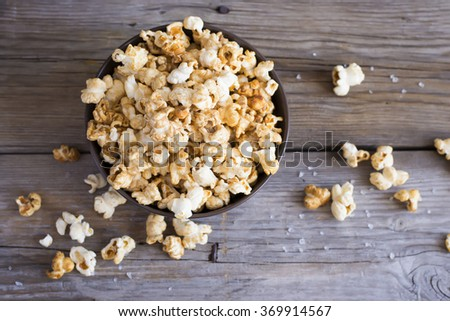 Salt popcorn on the wooden table, selective focus, top view - stock photo